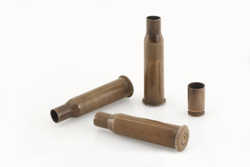 Three 7.62 mm caliber rifle and one 9 mm caliber pistol old sleeves (or bullet casings ) on an almost white background. Focus on full depth.