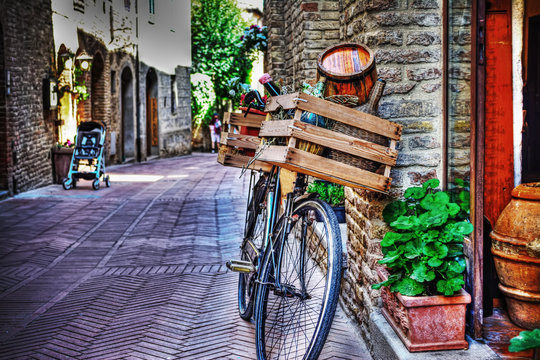 old bike with wooden case against a brick wall in San Gimignano