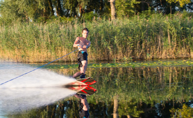 Wakeboarder athlete glides through the water with burning spray