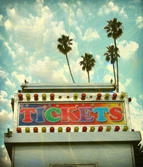 aged and worn vintage carnival ticket booth with palm trees