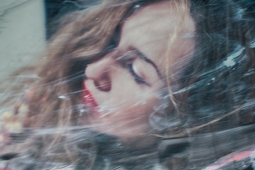 Portrait of a beautiful woman through the dirty glass