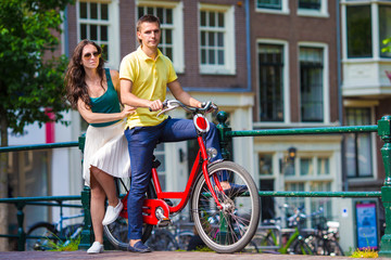 Young happy couple on bikes at bridge in Amsterdam