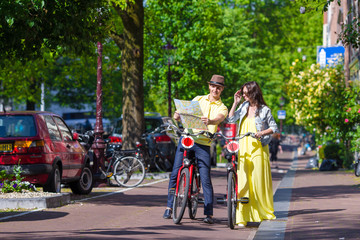 Young happy couple with city map on bikes in Amsterdam