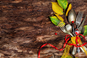Vintage silverware on rustic wooden background with autumn decoration