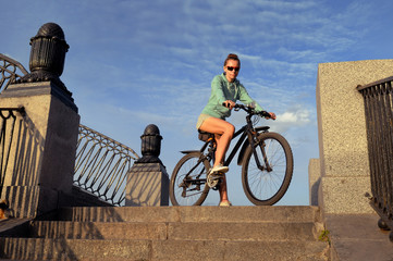 Young woman on a bicycle on the stone steps against the blue sky