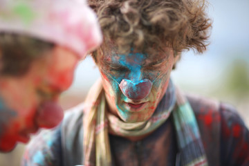 Painted face of a clown looking down, holi festival
