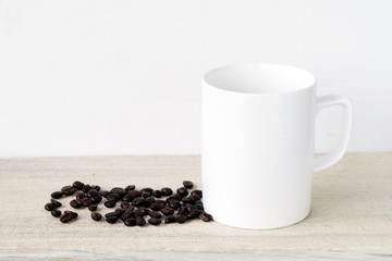 Coffee cup and saucer with coffee beans on wooden table