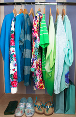 Colored female clothes on hangers in wardrobe