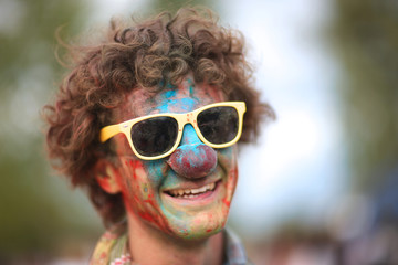 Happy curly man in sunglasses and clown nose covered with power paint