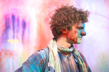 Profile of a curly clown covered with colorful powder at holi festival