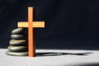 This shows a simple wooden cross standing next to a peaceful stack of smooth stones. The cross casts a shadow and appears to almost lean on the stones for support.