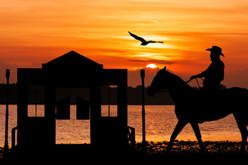 silhouette of Cowboy sitting on his horse at river sunset backgr