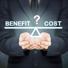 businessman holding benefit and cost seesaw