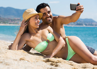 Happy couple taking photo on the beach.