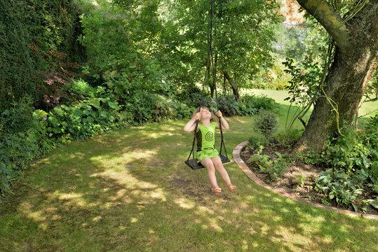 enfant à l'ombre sur une ballançoire