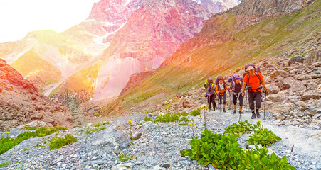 Group of people walking on trail. Men and women going up with backpack luggage and hiking gear on bright mountain landscape background with sun rising and high peaks behind