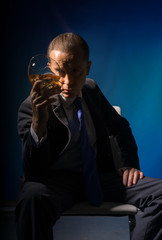 A man in a suit drinking brandy