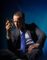 A man in a suit sitting with a glass of aged brandy.