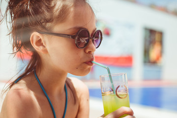 Female child drinking a cocktail in the pool