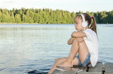 ГАРМОНИЯ/ Девочка слушает музыку сидя на деревянном мостике на озере.