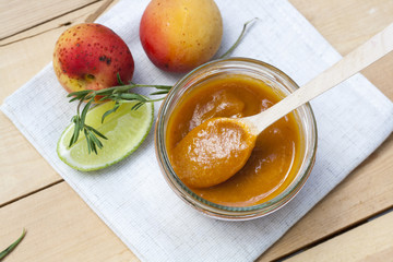 Homemade apricot jam and fresh apricots, lime and  rosemary with leaves on the wooden table
