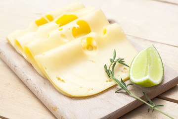 Maasdam several slices of cheese on wooden board, lime and rosemary