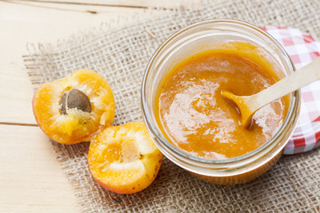 Homemade apricot jam and fresh apricots with leaves on the wooden table
