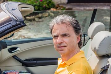Classy senior sportsman driving cabriolet car