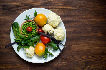 Photo of white plate with fresh vegetables. Top view