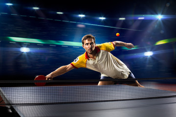 young sports man tennis player playing on black background with