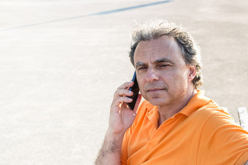 Classy senior sportsman talking on a mobile phone