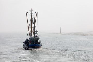 Kutter in  einer Fahrrinne bei Ebbe an der Nordsee bei Nebel