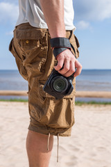 The memory of the holiday and the hot summer - a man and a camera. Man (male) dressed in shirt and breeches, red shoes, standing on the sandy shore of the sea and holding a camera