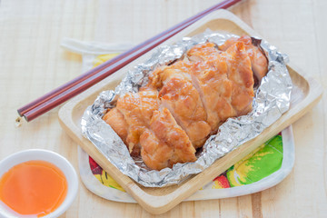 Baked chicken breast on wood table.