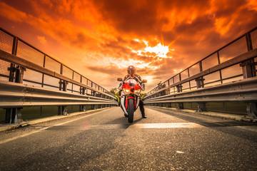 Moto da strada pronta alla partenza sotto un cielo rosso al tramonto
