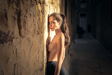 Naked beautiful girl standing against a wall