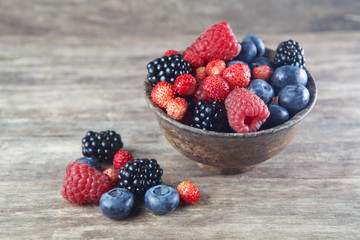 Assorted berries in bowl on wood