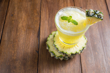 pineapple smoothie on wooden background