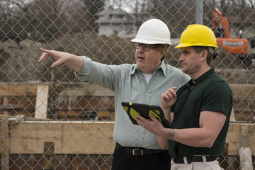Two workers on a construction site using a tablet