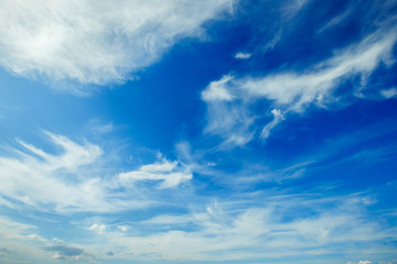 Horizontal image of white fluffy clouds on blue sky background