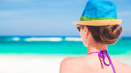 closeup back view of young woman in straw hat at tropical