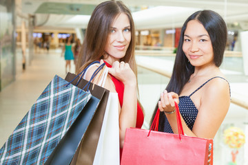 Two fashion girlfriends shopping at mall