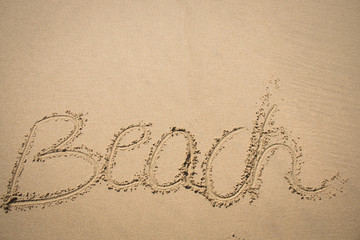 The word beach written in the sand on a beach in Mozambique