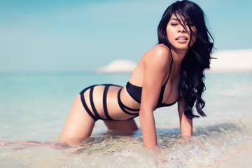 Girl kneeling on beach in water