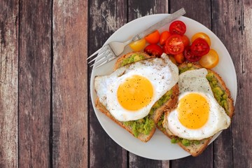 Healthy avocado, egg open sandwiches on a plate with colorful tomatoes against rustic wood
