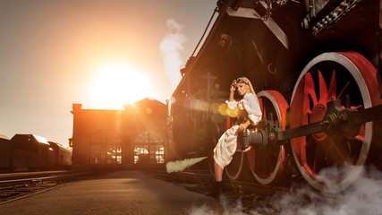 Woman in the vintage dress is sitting on the locomotive's wheel