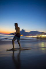 Action silhouette of Brazilian riding skimboard on Ipanema Beach Rio de Janeiro Brazil at sunset