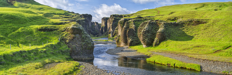 Spoed Fotobehang Canyon green hills of canyon with river and sky in Iceland