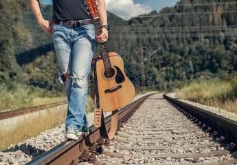 Close up image man legs in rippad denim walk on the railway