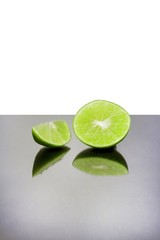 Lime slices on the mirror table and white background.